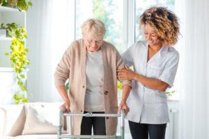 Nurse helps elderly woman with walker