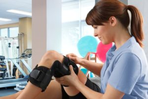Therapist Adjusting Patient's Knee Brace